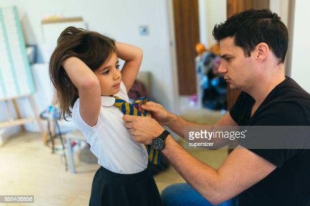 Father is preparing girl for school