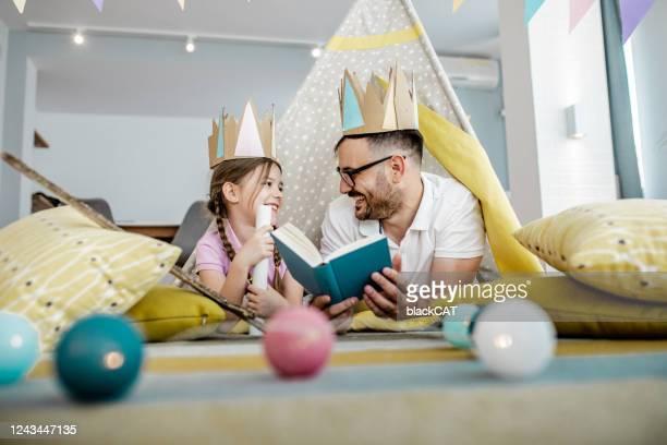 o pai está lendo um livro para a filha. - conto de fadas - fotografias e filmes do acervo