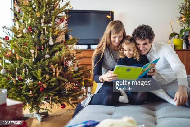 padre está leyendo un cuento de navidad - historia fotografías e imágenes de stock
