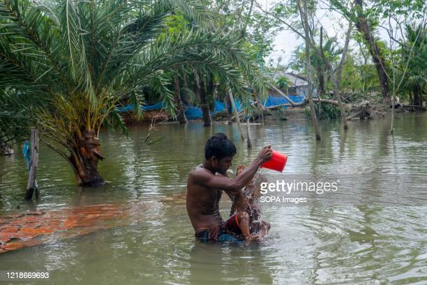 Father is seen bathing his child at the flooded shores after the landfall of cyclone Amphan during the aftermath. Thousands of shrimp enclosures have...