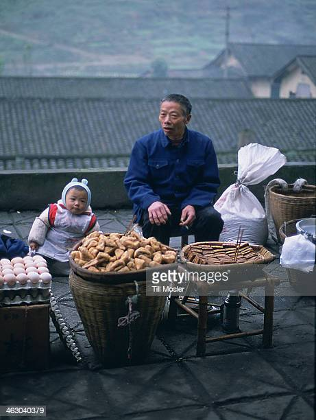 Father is selling torfu on a traditional, chinese local market in Sichuan province. China, April 2007