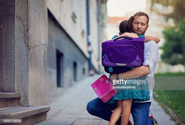 father is sending his sad daughter to school for first time and trying to relax her - first day of school stock pictures, royalty-free photos & images