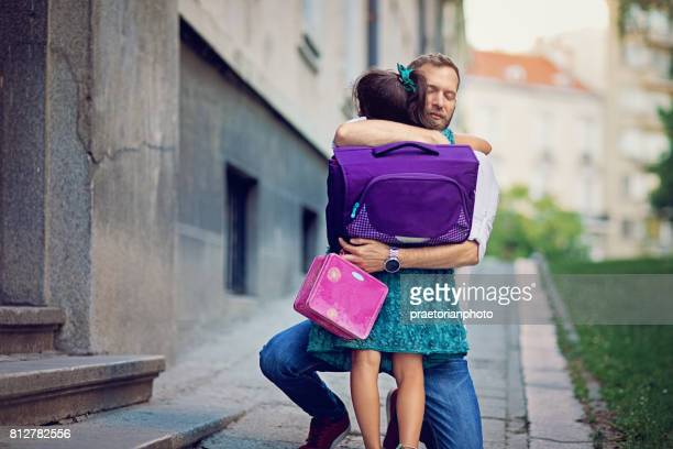 Father is sending his sad daughter to school for first time and trying to relax her