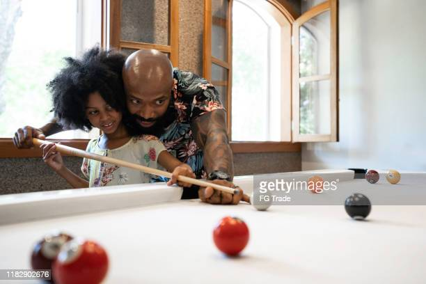 father is teaching daughter how to play snooker - kids pool games stock pictures, royalty-free photos & images