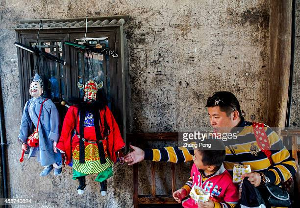WUZHEN TONGXIANG ZHEJIANG CHINA A father is teaching his child about Quanzhou Marionette Two Marionette characters is ready for puppetry show The...