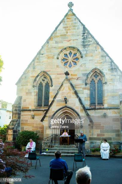 Father James Collins holds a service in the yard of St Paul's Anglican Church in Burwood with seating observant of social distancing on March 22 2020...
