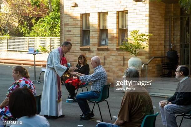 Father James Collins holds communion in one kind at a service in the yard of St Paul's Anglican Church in Burwood with seating observant of social...
