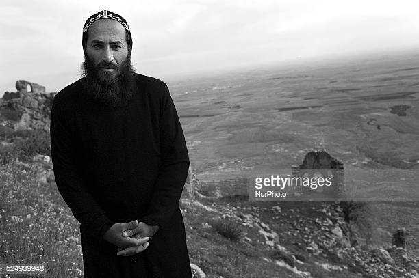 Father Joaqim stands by Mor Augen Monastery overlooking Syria and the Mesopatamian plain Mor Augen is an ancient Syriac Orthodox Monastery situated...