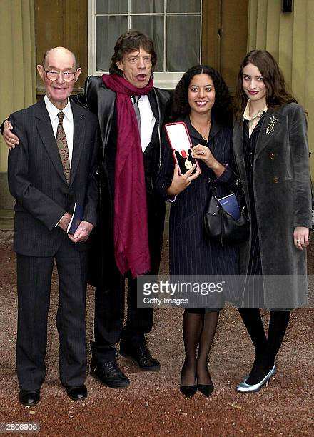 Father Joe with veteran rocker Sir Mick Jagger of the Rolling Stones and daughters Karis and Elizabeth at Buckingham Palace on December 12 2003 in...