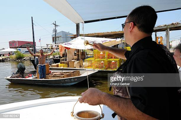 Father John Arnone pastor of St Bernard and Our Lady of Lourdes uses holy water to bless the boat of fisherman Darren Nunez for the 63rd Annual...
