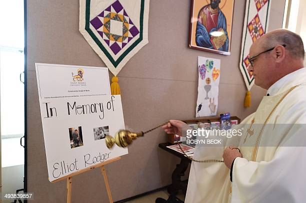Father John Love waves incense in prayer over photos of accused killer Elliot Rodger at a memorial service for those killed in a mass shooting...