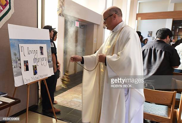 Father John Love waves incense in prayer over photos of shooting rampage victim Chris Michael-Martinez, at a memorial service for those killed in a...