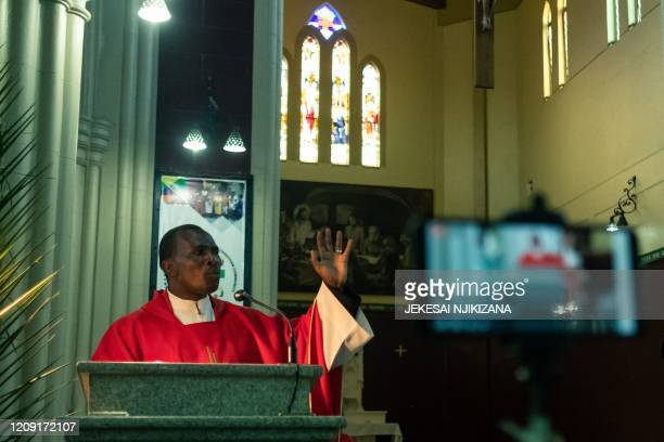 Father Kennedy Mugute the Vicar General of the Archdiocese of Harare conducts a Palm Sunday mass which is livestreamed to parishioners on Facebook in...