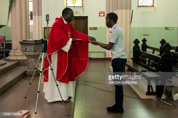 Father Kennedy Mugute, the Vicar General of the Archdiocese of Harare, gives communion to the head of media Ronald Mapfumo , as he conducts a Palm...