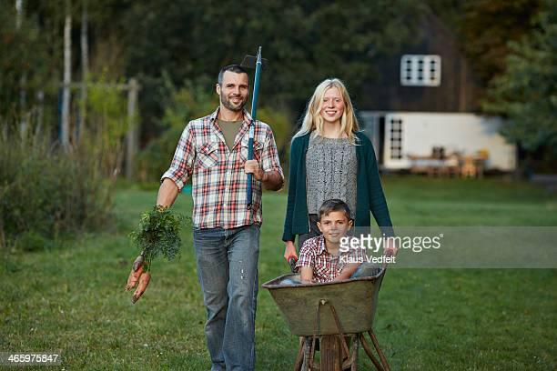 father & kids walking in garden - landwirtschaftliche tätigkeit stock-fotos und bilder