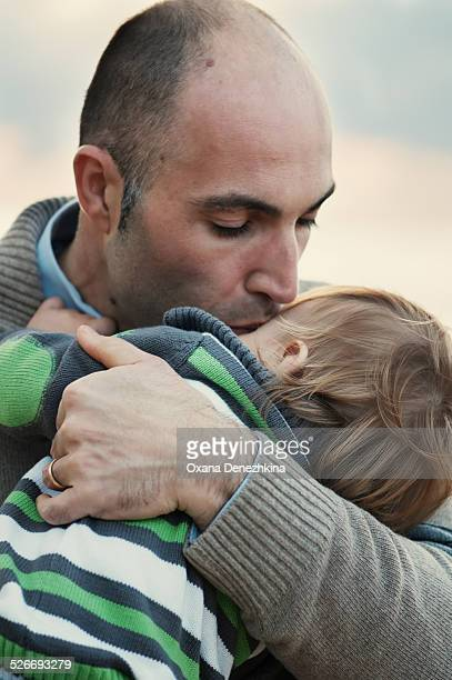father kissing a small son - genderblend stock pictures, royalty-free photos & images