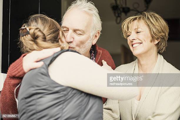 Father kissing adult daughter, mother smiling