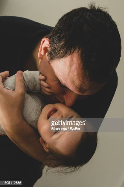 father kissing baby at home - unknown gender stock pictures, royalty-free photos & images