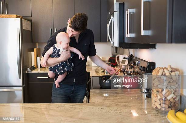 Father kissing baby daughter (2-5 months) while stirring food
