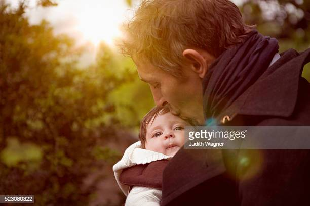 Father kissing baby (2-5 months)