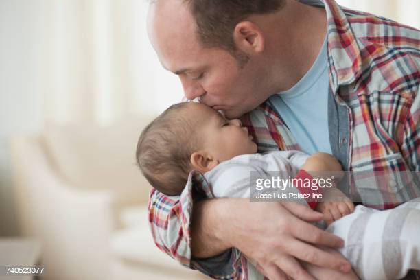 Father kissing baby son on forehead