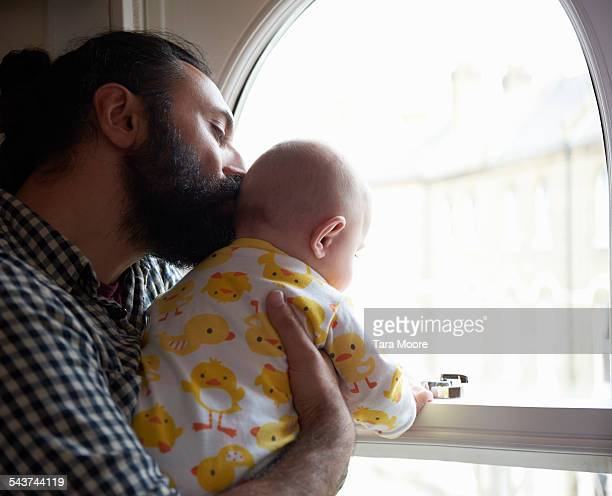 father kissing baby standing by the window at home - leanintogether stock pictures, royalty-free photos & images