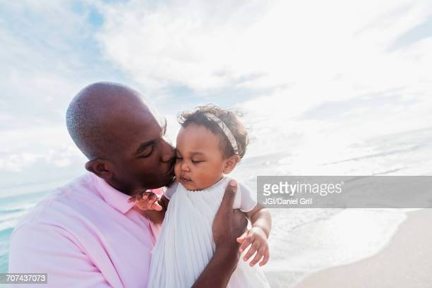 Father kissing cheek of baby daughter on beach