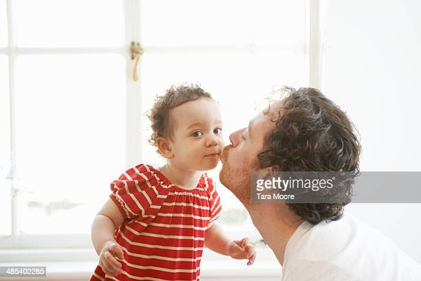 father kissing child