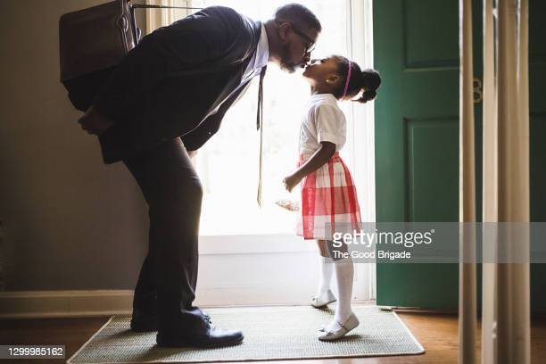father kissing daughter goodbye as he leaves for work - genderblend stock pictures, royalty-free photos & images