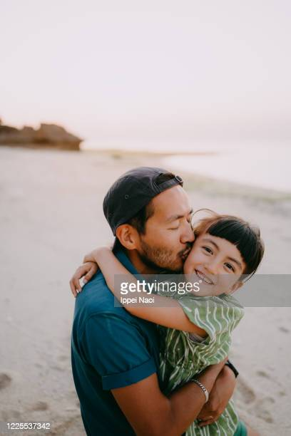 father kissing daughter on beach at sunset, japan - ippei naoi stock pictures, royalty-free photos & images