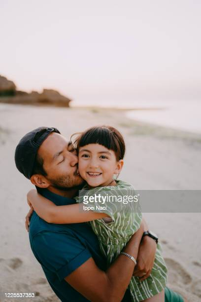 father kissing daughter on beach at sunset, japan - kissing stock pictures, royalty-free photos & images