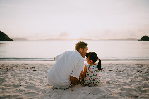 Father kissing daughter on beach at sunset, Okinawa, Japan - gettyimageskorea