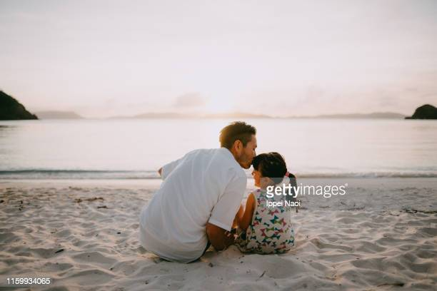 father kissing daughter on beach at sunset, okinawa, japan - travel stock pictures, royalty-free photos & images