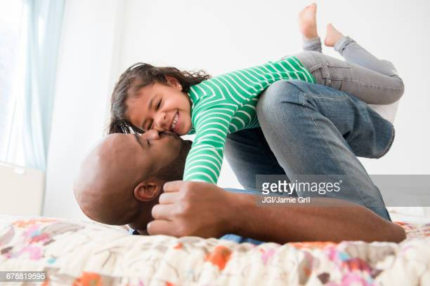 Father kissing daughter on bed