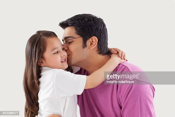 father kissing daughter on cheeks - indian girl kissing stock photos and pictures