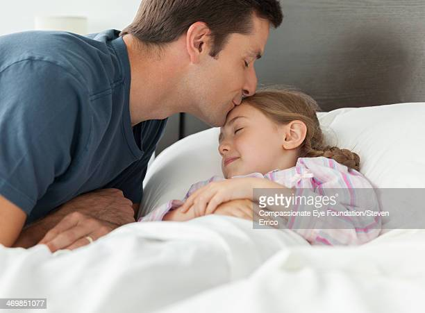 Father kissing daughter on forehead in bedroom