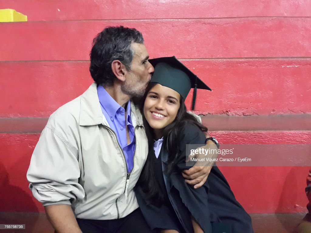 Father Kissing Graduate Daughter While Sitting Against Red Wall : Stock Photo