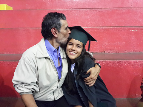 Father Kissing Graduate Daughter While Sitting Against Red Wall - gettyimageskorea