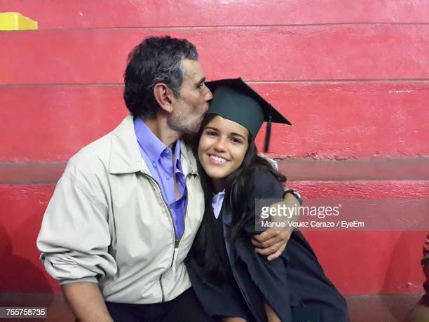 father kissing graduate daughter while sitting against red wall - father daughter stock pictures, royalty-free photos & images