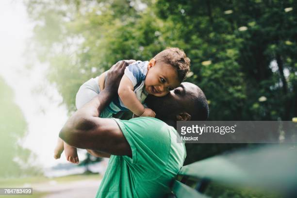 father kissing happy son while carrying at park - stay at home father stock pictures, royalty-free photos & images