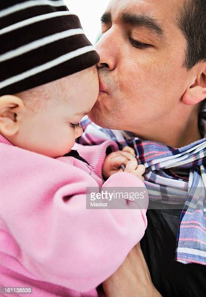 father kissing his daughter (0-11 months) on the forehead - 0 11 monate stock-fotos und bilder