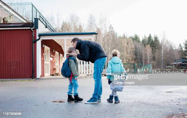 father kissing his kids goodbye at the school gates - sweden stock pictures, royalty-free photos & images