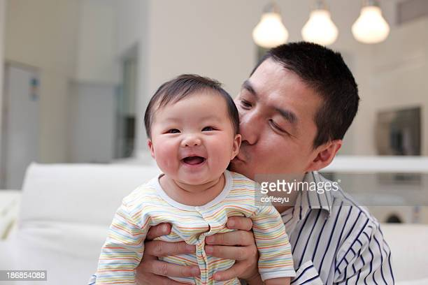 father kissing his laughing baby