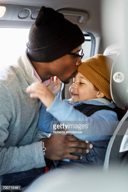 Father kissing son in car seat on forehead