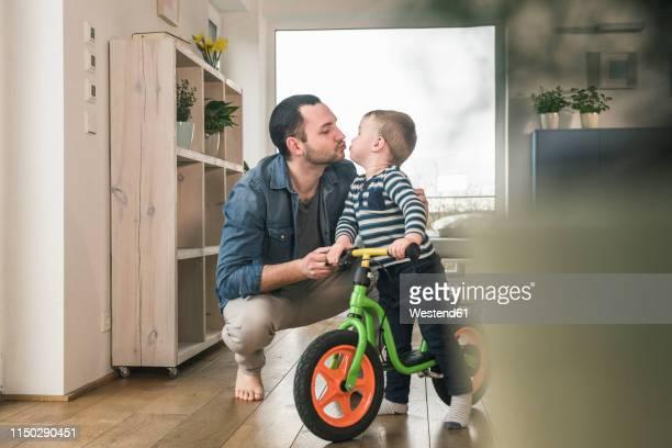 father kissing son with a balance bicycle at home - incoraggiamento foto e immagini stock