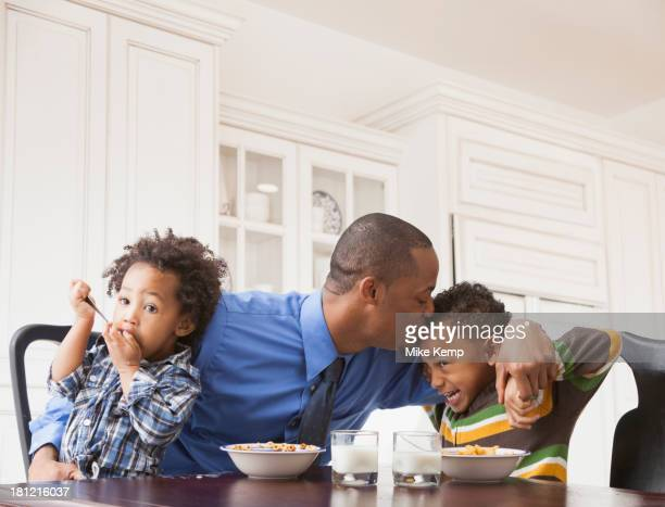 Father kissing sons at breakfast table