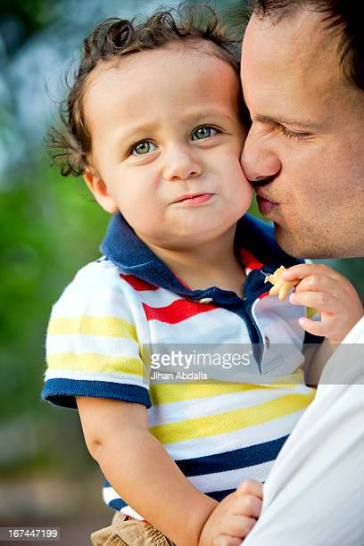 Father kissing son's cheek