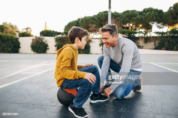 father lacing son's shoe on basketball outdoor court - basketball shoe stock photos and pictures