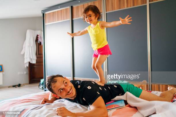 father laughing as his young daughter attempts to give him a massage - massage funny stock pictures, royalty-free photos & images