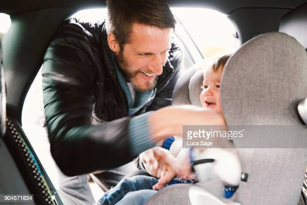 father laughs as he straps in his young toddler boy into his car seat - family inside car stock photos and pictures